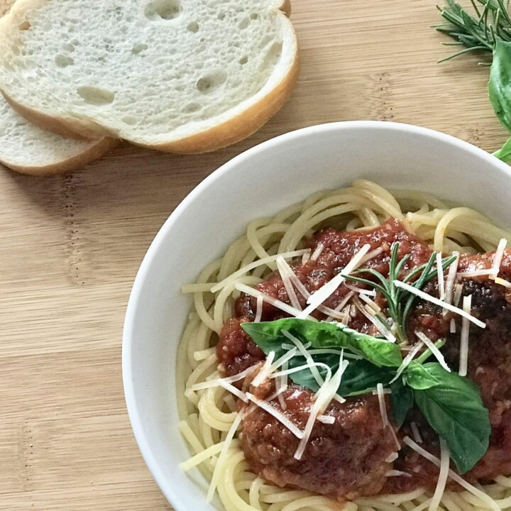 Marinara over pasta with shaved Parmesan Cheese and bread slices