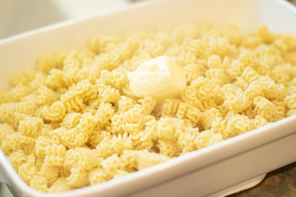 melt butter in warm pasta in baking dish
