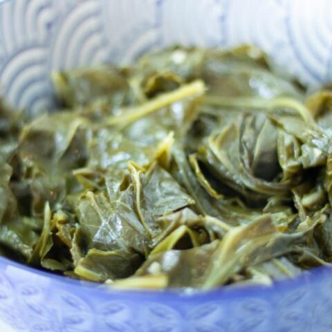 cooked collard greens in a blue and white patterned bowl.