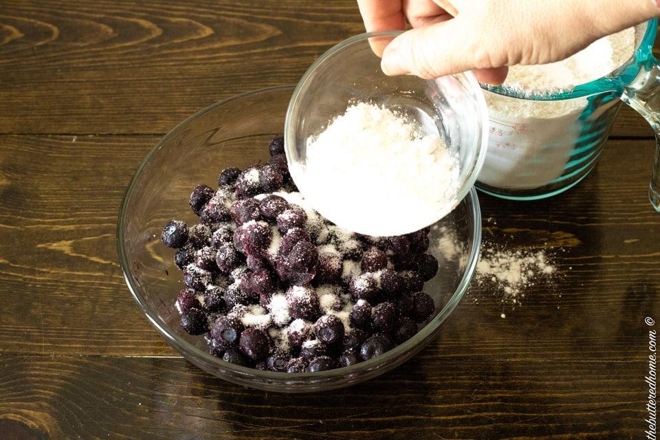 adding flour to blueberries