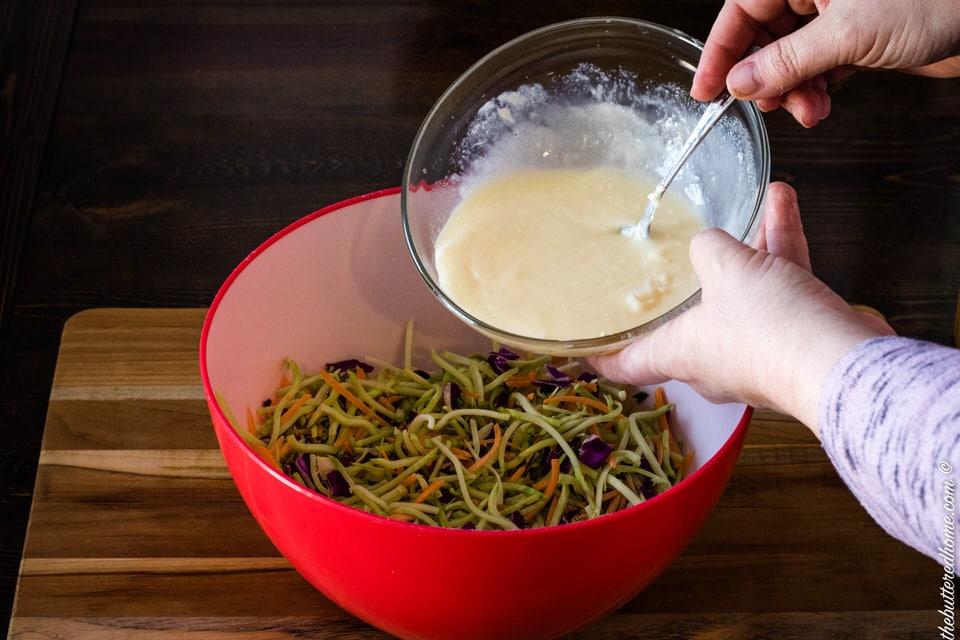 adding dressing to coleslaw vegetables