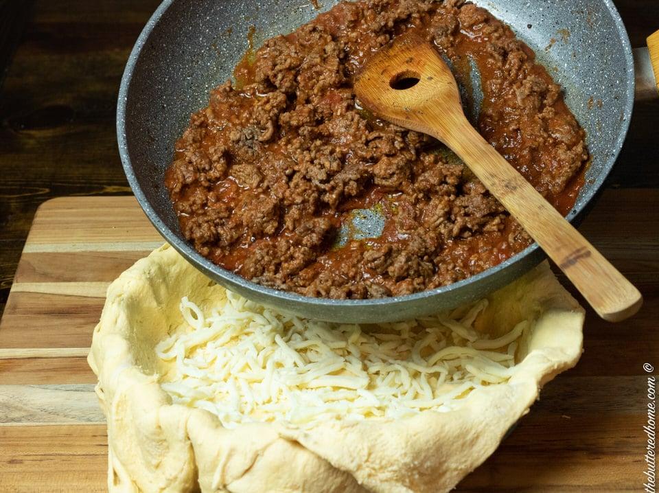 adding meat spaghetti sauce mixture to crescent crust