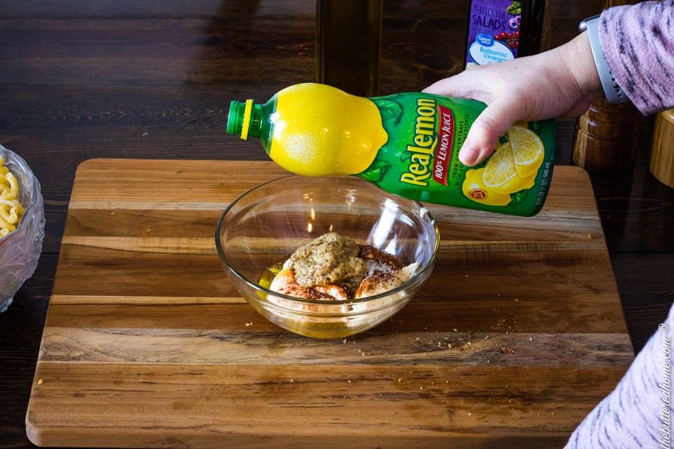 adding lemon juice to macaroni salad dressing