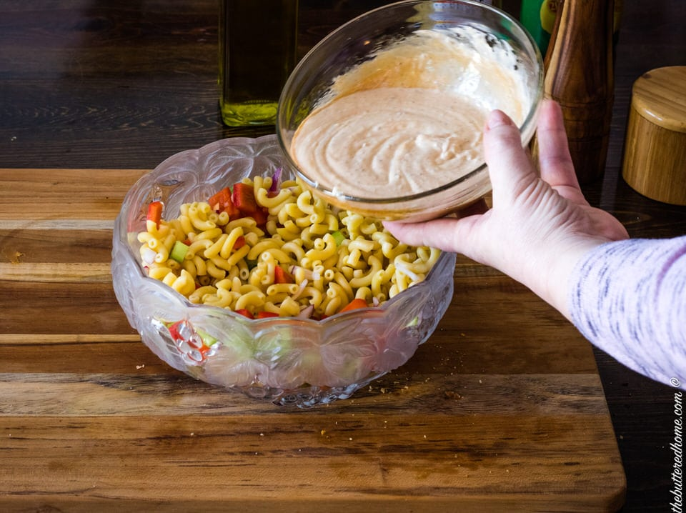 adding dressing to macaroni salad