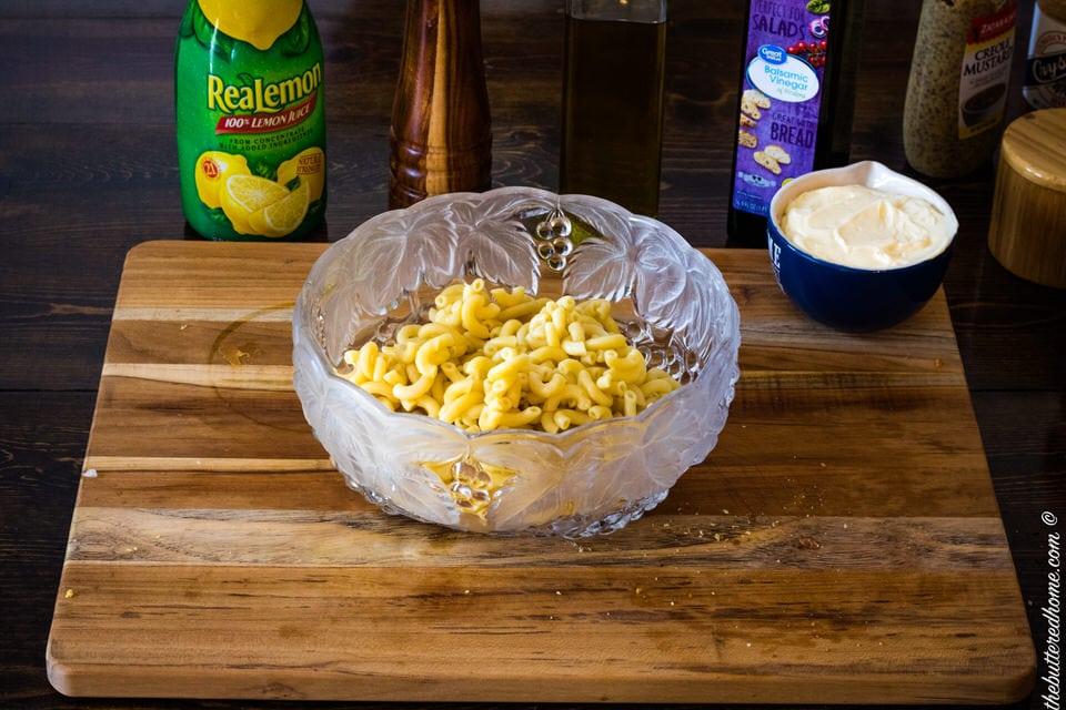 adding cooked macaroni pasta to macaroni salad
