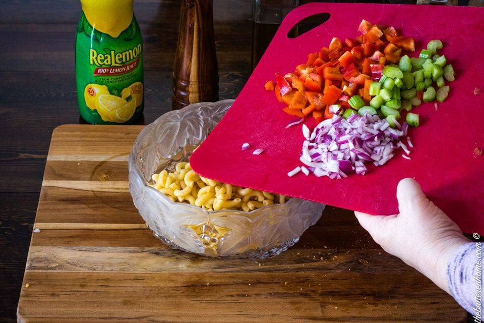 adding onions and peppers to macaroni salad