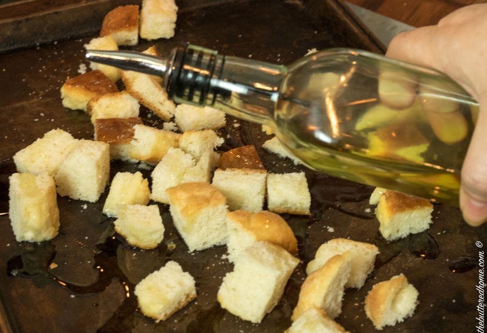 Olive oil being drizzled over cut up biscuit pieces for croutons