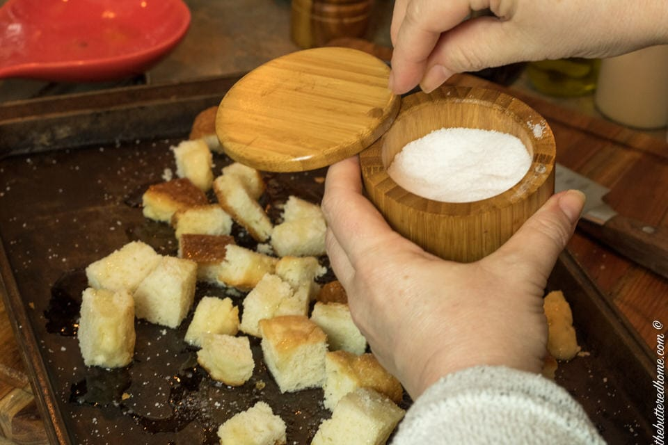 salt being sprinkled over cut up biscuit pieces for croutons
