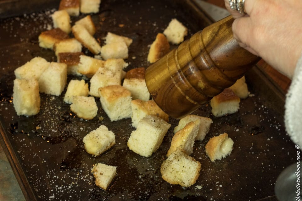 pepper being freshly cracked over cut up biscuit pieces for croutons