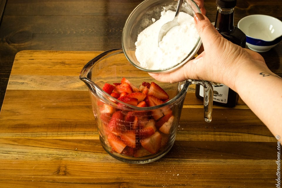sugar and cornstarch being added to fresh strawberries