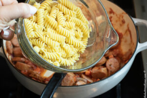 adding cooked rigatoni pasta to sausage