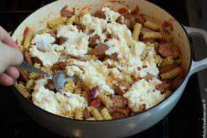 ricotta, parmesan and mozzarella cheese mixture being spread on sausage and pasta