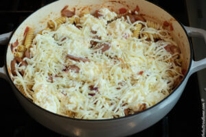 added cheese on top of sausage and pasta before baking in oven