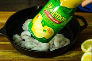 adding lemon juice to shrimp