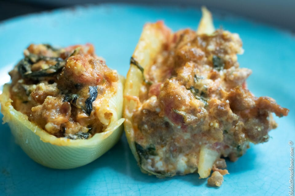 close up ofsausage and spinach stuffed shells on a blue plate