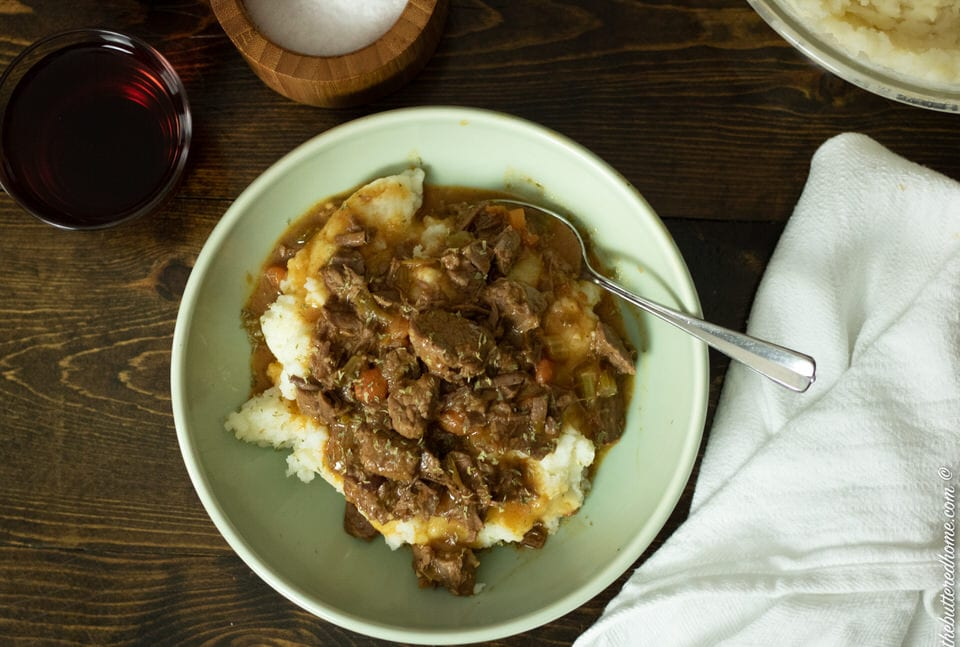 smothered beef tips in a green bowl on a dark wood table with a spoon and napkin