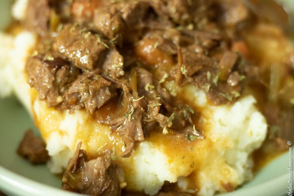 extra close up shot of smothered beef tips over mashed potatoes