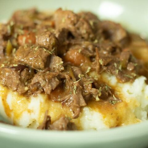 close up of smoother beef tips on bed of mashed potatoes in a green bowl