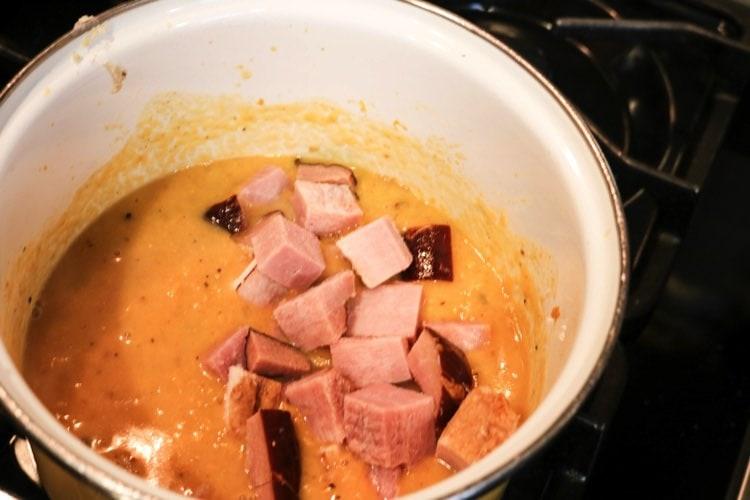 adding ham to sweet potato soup