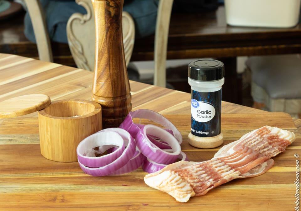 bacon raw, garlic powder, red onions salt and pepper on a wood board