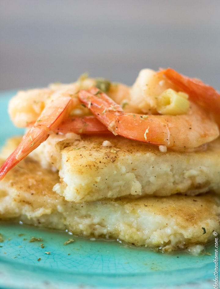 two grit cakes stacked on a blue plate with cooked shrimp on top