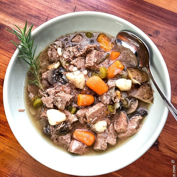 bow of instant pot rosemary beef stew with a fresh sprig of rosemary