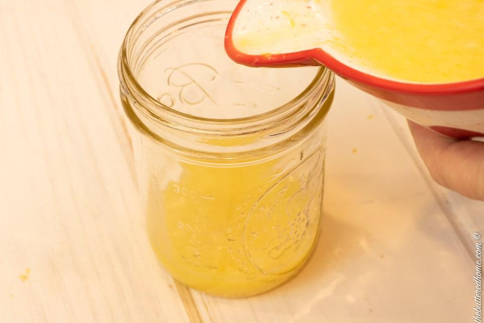 pouring lemon curd mixture into jar