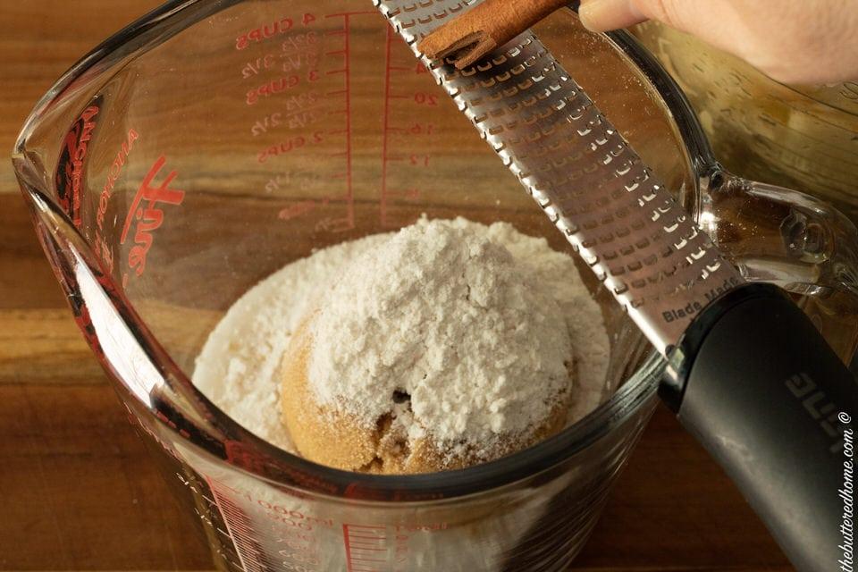 grating cinnamon into dry ingredients