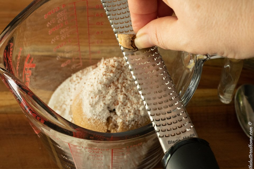 grating nutmeg into dry ingredients