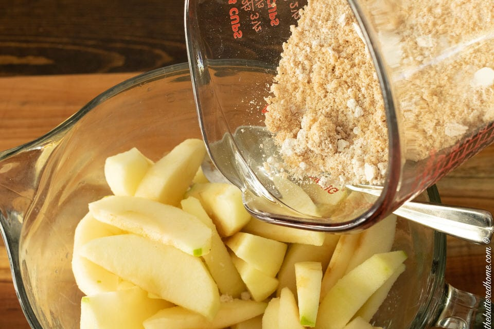 sprinkling dry ingredients over sliced apples