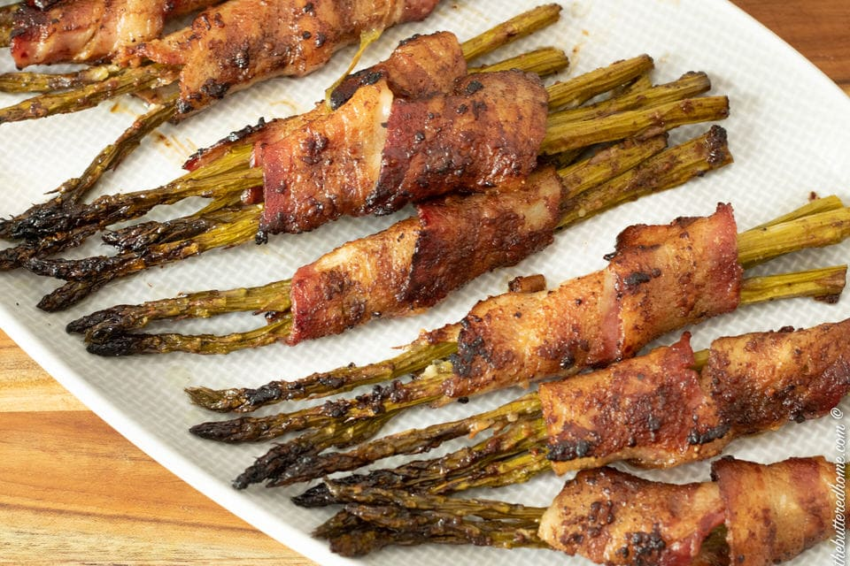 baked bacon wrapped asparagus on a gray plate