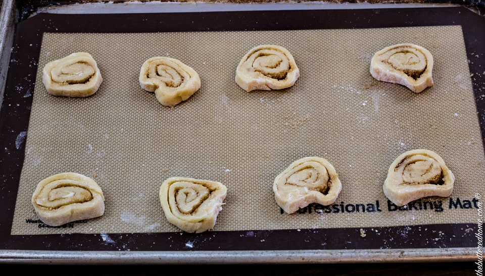 cinnamon roll cookies on a sheet pan with baking mat