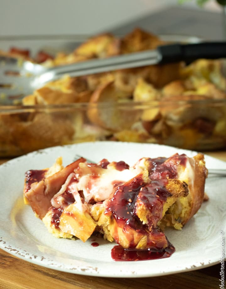 monte cristo casserole with raspberry sauce on a gray plate