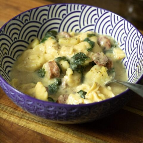 close up of spinach sausage and tortellini soup