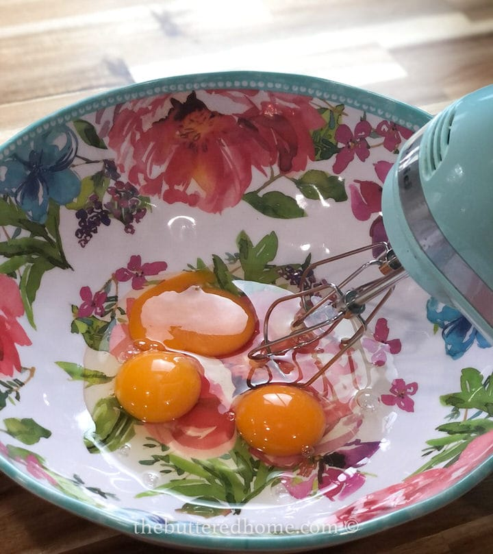 beating eggs in a floral colored bowl