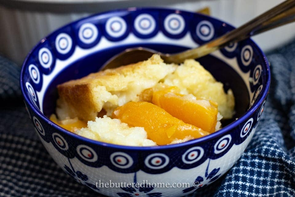 close up of peach cobbler in a blue and white bowl