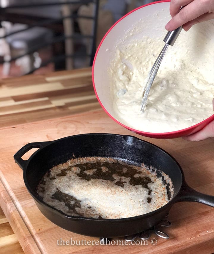 adding batter to hot oil in iron skillet