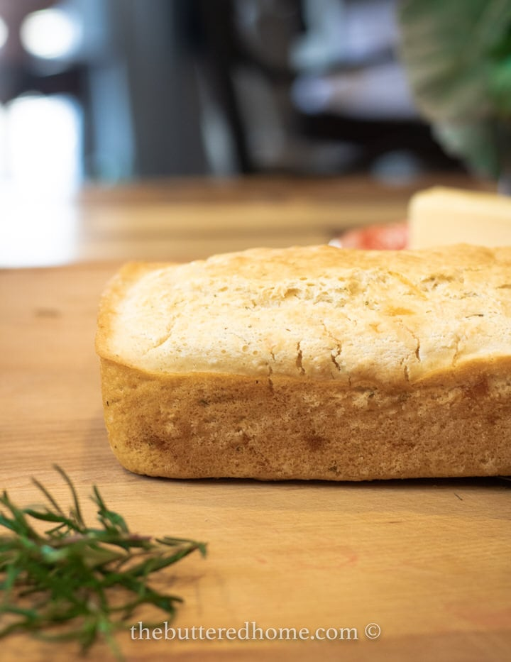 loaf of rosemary bread with rosemary on wood board