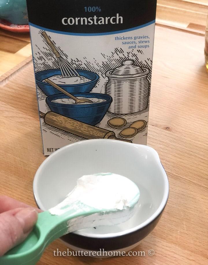 adding cornstarch to small bowl