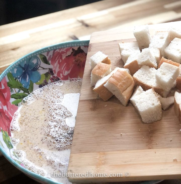 adding bread to milk mixture in floral bowl
