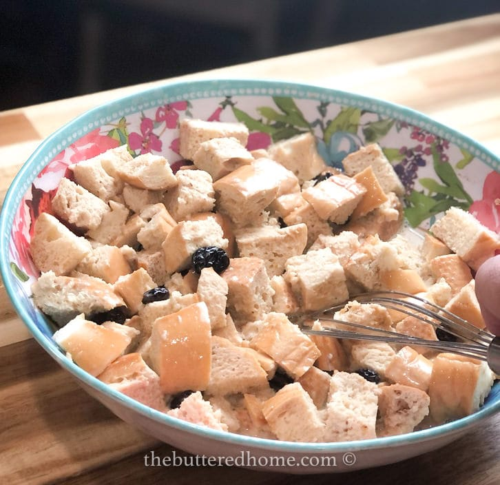 bread, raisins, milk mixture and bourbon in a floral bowl