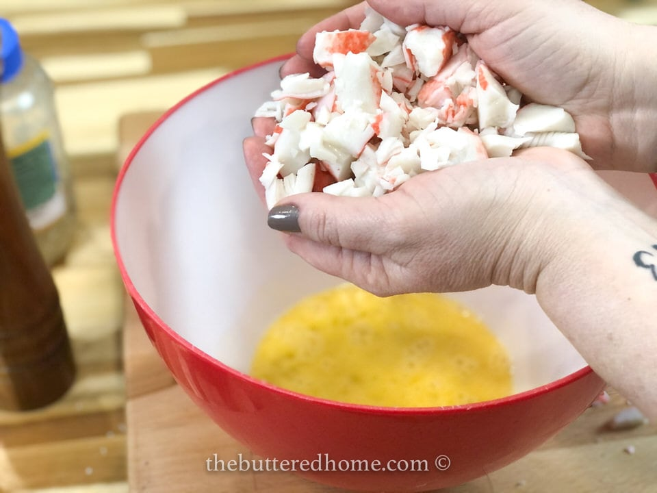 adding crab meat to eggs