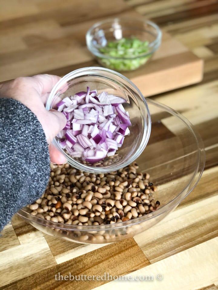 adding chopped onions to black eyed peas