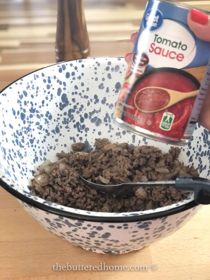adding tomato sauce to beef