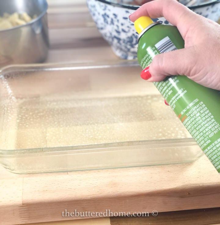 spraying casserole dish with non stick spray
