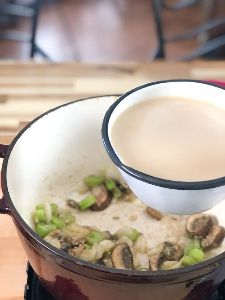 adding broth and milk to mushrooms and vegetables
