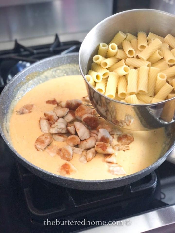 adding pasta to beschamel sauce and chicken
