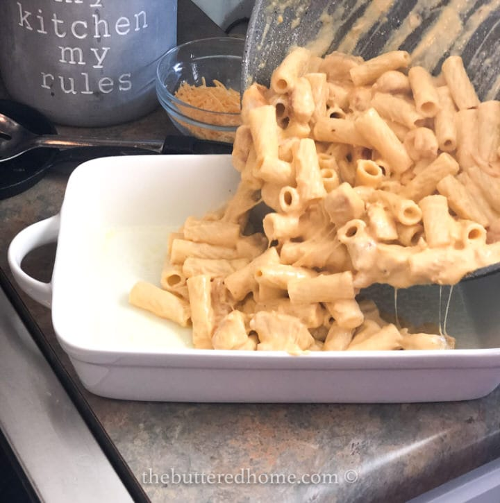 adding cooked pasta and fried chicken pieces to casserole dish
