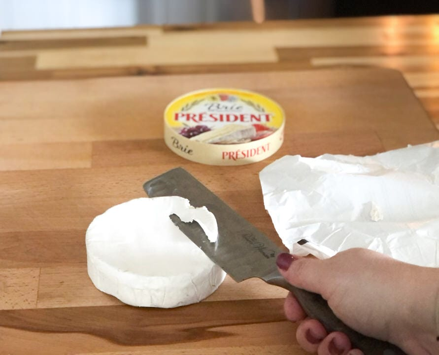 removing the rind off of brie carefully with a knife