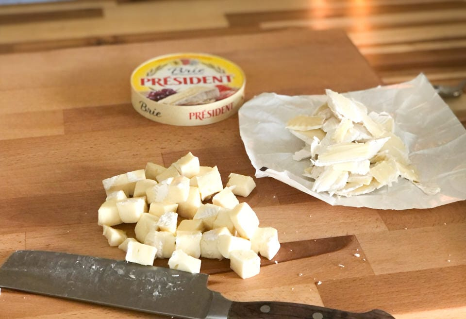 a wheel of brie that the rind has been removed and the cheese has been cubed